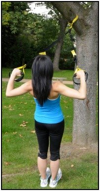 A woman doing a standing row with TRX fitness equipment.